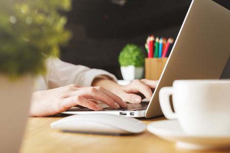 Photo pour Close up and side view of female hands typing on laptop keyboard placed on wooden desktop with decorative plants and coffee cup - image libre de droit