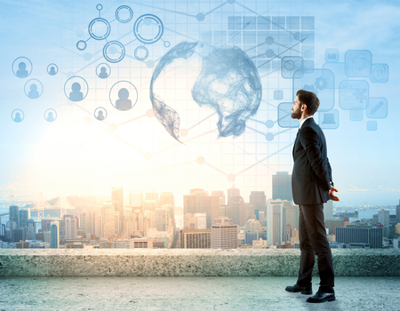 Side view of handsome young man standing on rooftop with digital charts, globe, HR and other icons. City view background. International business concept