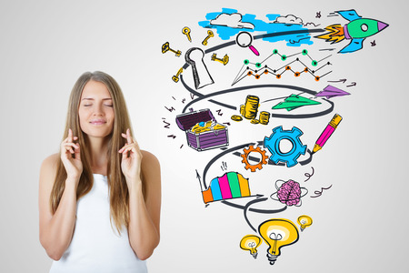 Photo pour Happy young female with crossed fingers on light background with colorful business sketch. Successful startup concept - image libre de droit