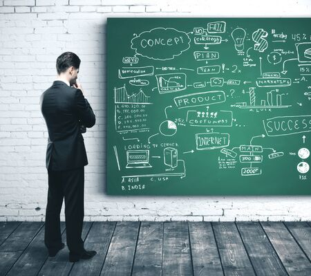 Foto de Businessman looking on blackboard with stock market report. Business success concept - Imagen libre de derechos