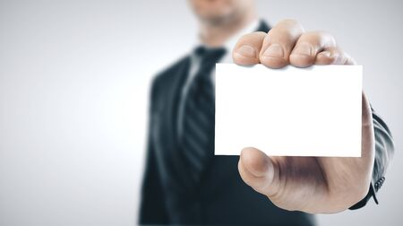 Photo pour Businessman holding a blank business card. Business success concept. Close up - image libre de droit