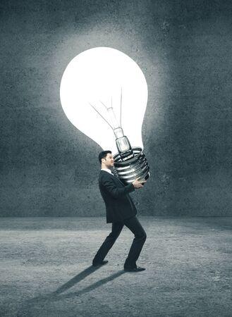 Photo pour Young businessman holding big lightbulb in concrete interior.  Business success concept. - image libre de droit