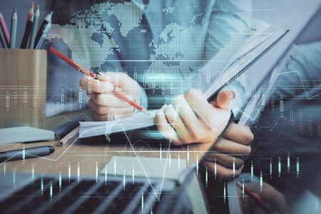 Photo pour A woman hands writing information about stock market in notepad. Forex chart holograms in front. Concept of research. Multi exposure - image libre de droit