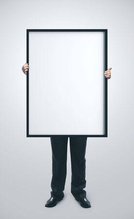 Photo pour Businessman holding blank poster on gray background. Business education concept - image libre de droit