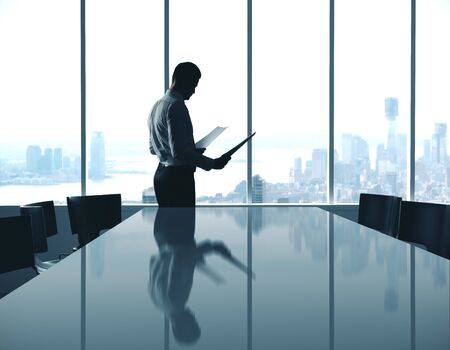 Photo pour Businessman with document standing in modern conference interior room with city view. - image libre de droit