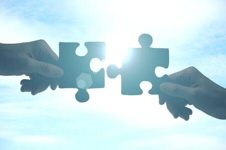 Photo pour Hands putting puzzle pieces together on sky background with sunlight. Partnership concept - image libre de droit