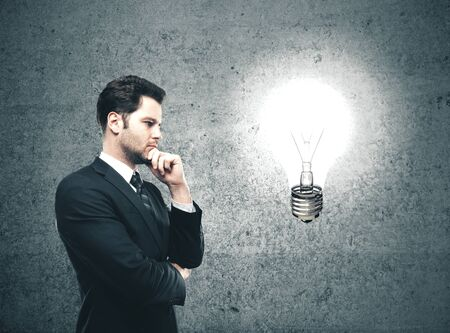 Photo for Businessman looking on glowing lamp Success and startup concept. - Royalty Free Image