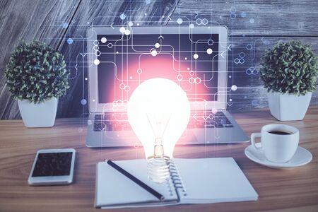 Photo pour Computer on desktop in office with bulb icon hologram. Multi exposure. Concept of idea. - image libre de droit