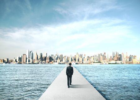 Photo pour Businessman walking to modern city on concrete bridge. Business and challenge concept. - image libre de droit