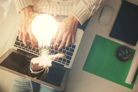 Photo pour Double exposure of woman hands working on computer and light bulb hologram drawing. Top View. Idea concept. - image libre de droit
