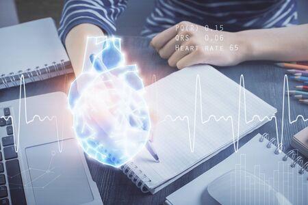 Photo pour Heart hologram over womans hands writing background. Concept of Medical study. Multi exposure - image libre de droit