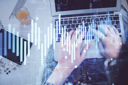 Photo pour Double exposure of man's hands typing over laptop keyboard and forex chart hologram drawing. Top view. Financial markets concept. - image libre de droit