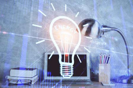 Photo pour Computer on desktop in office with bulb icon hologram. Double exposure. Concept of idea. - image libre de droit