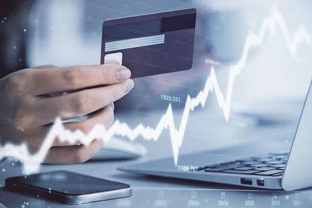 Foto de Multi exposure of woman on-line shopping holding a credit card and financial graph drawing. Stock market E-commerce concept. - Imagen libre de derechos