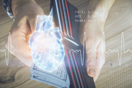 Photo pour Multi exposure of heart drawing hologram and USA dollars bills and man hands. Medical education - image libre de droit