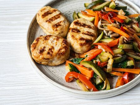 Photo pour Turkey cutlets grill, vegetables steer fry on a plate on wood board table. - image libre de droit