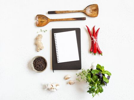 Foto de Kitchen background with open cookbook for recipes and various spices and herbs on light background. Top view. Copy space - Imagen libre de derechos
