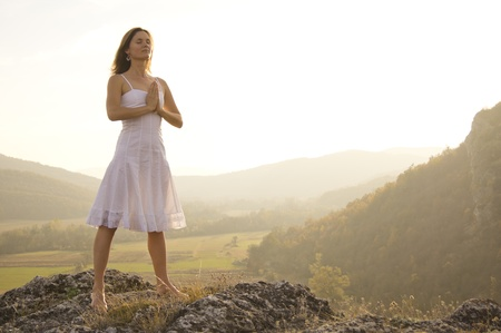 Young woman standing in meditation on the top of a hill