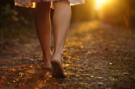 Foto de Young female legs walking towards the sunset on a dirt road - Imagen libre de derechos