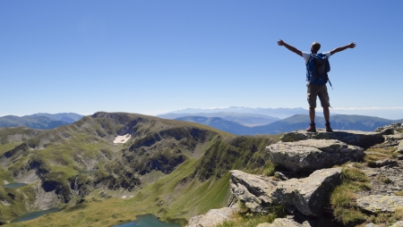 Male hiker in Rila mountains, Bulgaria, with arms stretched out to enjoy the mountain scenery