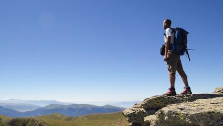 Male hiker standing with backpack on rock overlooking mountain range