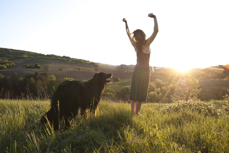 Beautiful woman raises her arms to the sun in joy whilst walking her dog