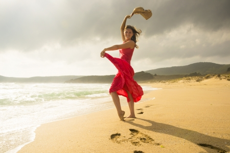 Beautiful happy young woman dancing on a sunny sandy beach