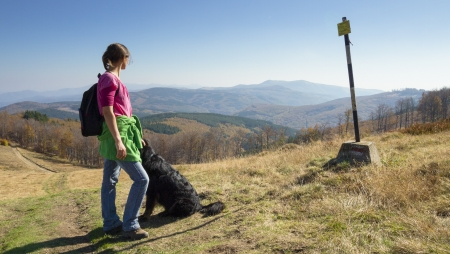 Slim young girl walking in the mountains with her dog looking at a singpost