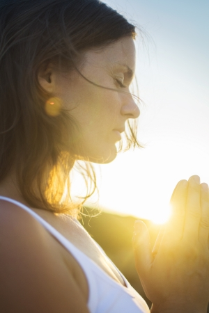 Beautiful young woman in silent meditation and prayer connected in the spirit with the universal love of God.
