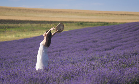 Photo for Beautiful young woman wearing a white dress celebrating the beauty of life standing in the middle of a lavender field in bloom. - Royalty Free Image