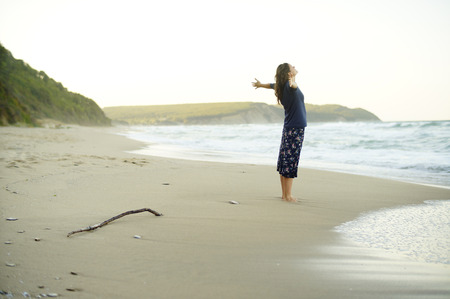 Photo for Beautiful young woman with her arms up enjoying the sense of freedom on a desolate beach. - Royalty Free Image