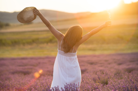 Photo for Beautiful young woman with a white dress and a straw hat standing in the middle of a lavender field at in the golden light of the sunset praising the beauty of life. - Royalty Free Image