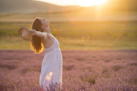 Photo pour Beautiful young woman with a white dress and a straw hat standing in the middle of a lavender field at in the golden light of the sunset praising the beauty of life. - image libre de droit