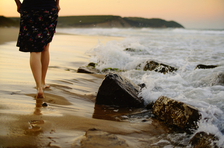 Foto de Female legs walking on the beach on a warm summer evening. - Imagen libre de derechos