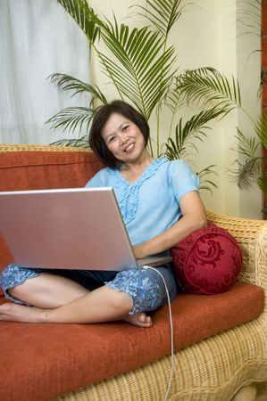 Woman sitting on her sofa and working with computer