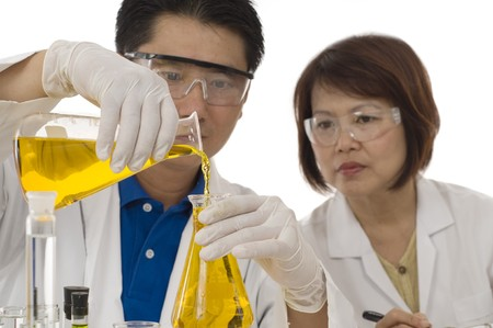 Scientist team  pouring chemicals in a laboratory