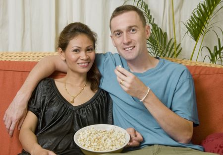Young interacial couple sitting together eating popcorn