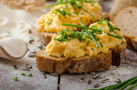 Scrambled eggs with herbs on wheat-rye crispy bread, homemadeの写真素材