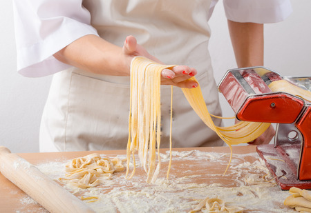 Photo for Young woman chef prepares homemade pasta from durum semolina flour - Royalty Free Image