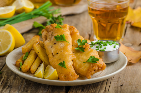 Foto de Fish and chips. Fish wrapped in beer batter, herbs dip and czech beer - Imagen libre de derechos