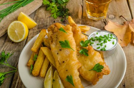 Foto de Fish and chips. Fish wrapped in beer batter, herbs dip and czech beer - Imagen libre de derechos