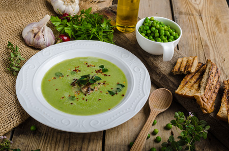 Soup of young peas, with little garlic, roasted nuts and panini toastsの写真素材