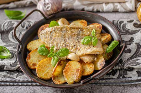 Foto de Delicious fish with roasted potatoes and bio garlic - Imagen libre de derechos