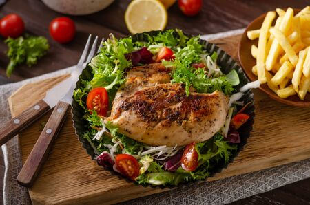Photo pour Fresh salad with tomatoes, grilled chicken and homemade french fries - image libre de droit