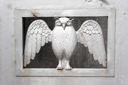 minerval owl on belgian cemetery gate