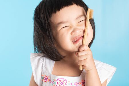 Photo pour Cute Asian girl holding a toothbrush to clean her teeth on a blue background and copy space. - image libre de droit