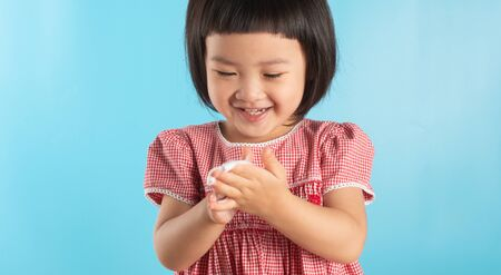 Photo pour Cute Asian girl washing hands with soap bubbles to kill bacteria COVID - 19 for good health with fun and happiness. With copy space. - image libre de droit