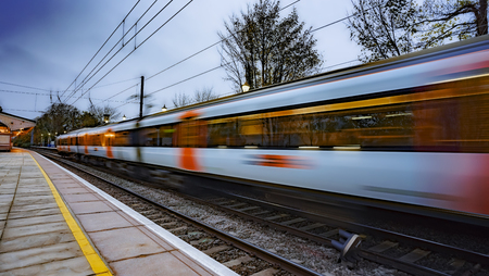 UK commuter train passing through a station at dusk
