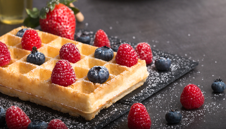 Freshly baked Brussels waffles on a black stone plate with fresh strawberry's and blueberry's and raspberry's on a dark stone table with honey and coffee.