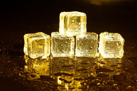 Photo pour ice cubes on a reflections yellow light. - image libre de droit